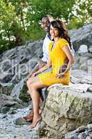 Happy couple sitting at rocky shore