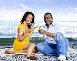 Happy couple having wine on beach