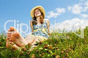 Young barefoot girl sitting in meadow