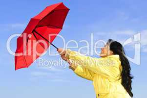 Beautiful young woman in raincoat with umbrella