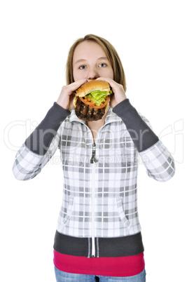 Teenage girl eating big hamburger