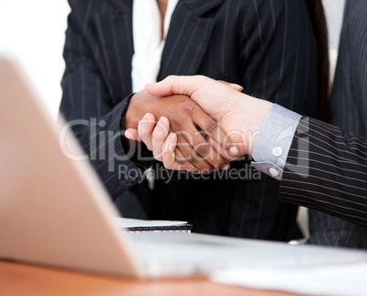 Close-up of a handshake between two businessmen with laptop