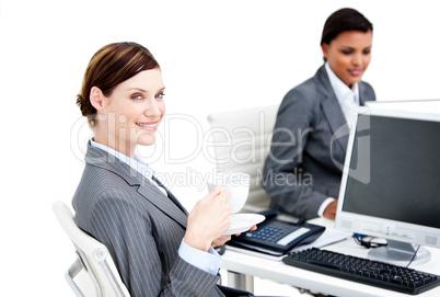 Smiling female business partners having a break drinking coffee