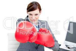 Confident businesswoman punching with boxing gloves