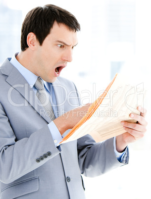 Portrait of a surprised businessman reading a newspaper