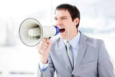Portrait of an angry businessman using a megaphone