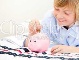 Cute boy putting a coin in a piggybank