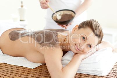 Happy woman enjoying a mud skin treatment