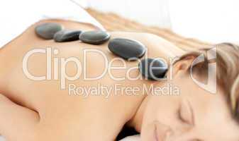 Relaxed woman with hot stones on her back