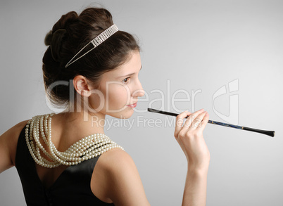Elegant girl with cigar-holder, side view