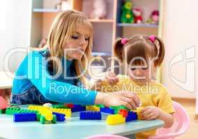 Teacher and preschooler play with building bricks