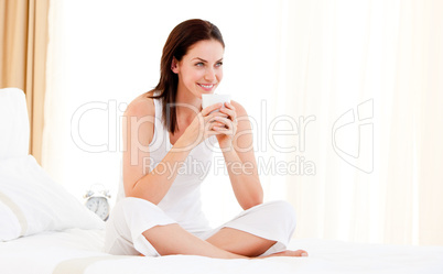Beautiful woman drinking a coffee sitting on her bed