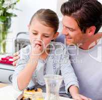 Jolly father and his daughter having breakfast together