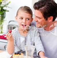 Smiling father and his daughter having breakfast together