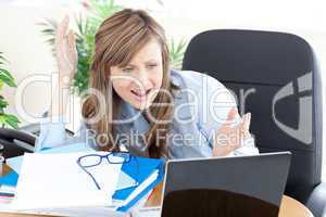 Angry businesswoman looking at the laptop
