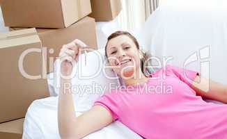 Self-assured woman relaxing on a sofa with boxes