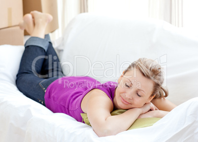 Portrait of a cheerful woman relaxing on a sofa with boxes