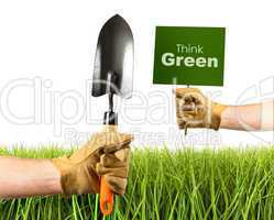 Hands holding garden trowel and sign