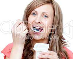Lively woman eating a yogurt