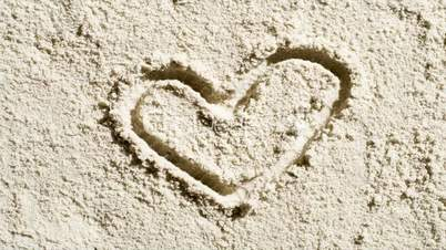 A love heart erodes in sand