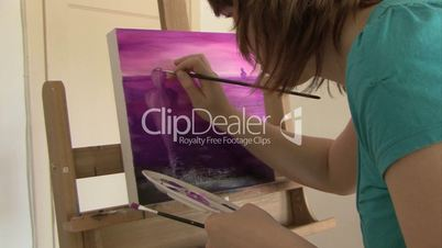 artist paints purple painting on a canvas