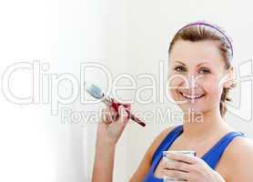 Smiling woman is decorating a room