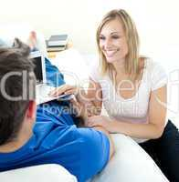 Caucasian couple using a laptop together on a sofa