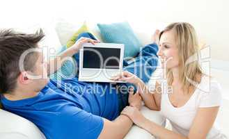 Charming couple using a laptop together on a sofa