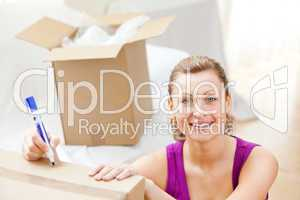 Cute woman writing on boxes using a pen