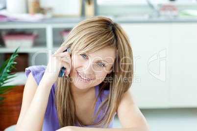 Delighted woman talking on the phone in the kitchen