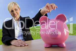 Woman Putting Coin Into Pink Piggy Bank In Green Field