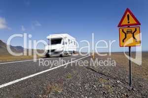 Motor Home Driving On An Open Road With Danger Sign