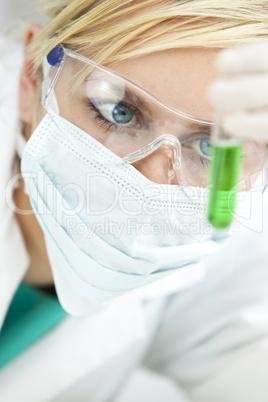 Female Scientific Researcher With Green Solution In Laboratory
