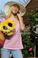 Beautiful Girl On Cell Phone With Sun Hat and Sunflowers