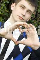 Teen boy making heart shape with hands