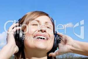 Cheerful woman listenng music outdoors