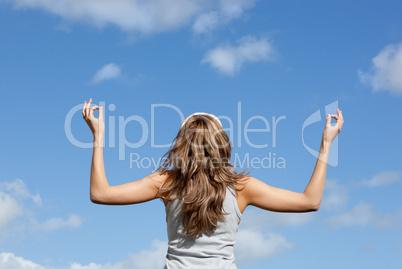 Caucasian woman meditating against a blue sky