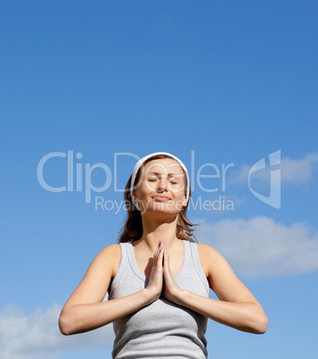 Radiant woman meditating against a blue sky