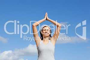 Cheerful woman meditating against a blue sky
