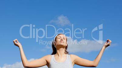 Peaceful woman meditating against a blue sky