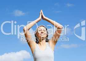 Cheerful woman doing yoga against blue sky