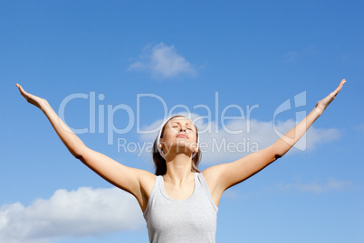 Peaceful woman relaxing against blue sky