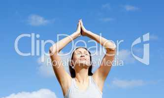 Relaxed woman doing yoga against blue sky