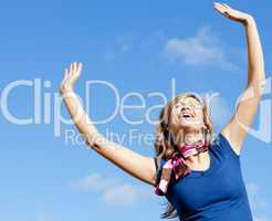 Delighted blond woman punching tha air against blue sky