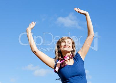 Bright blond woman punching tha air against blue sky