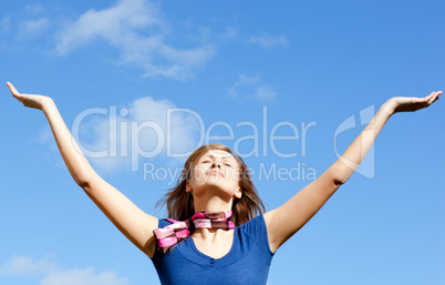 Radiant blond woman punching tha air against blue sky
