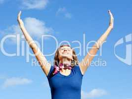 Jolly  blond woman punching tha air against blue sky