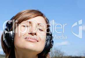 Relaxed woman listenng music outdoors