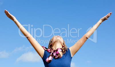 Relaxed  blond woman punching tha air against blue sky