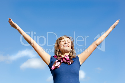 Young  blond woman punching tha air against blue sky